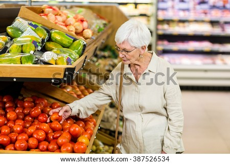 Senior woman choosing her tomatoes in supermarket