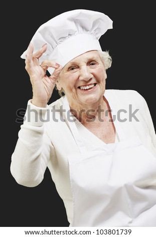 senior woman cook doing an excellent symbol against a black background