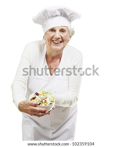 senior woman cook holding a bowl with salad against a white background