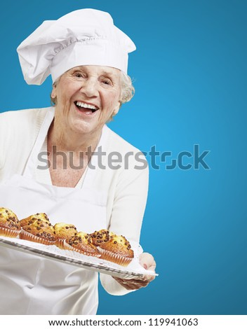 senior woman cook holding a tray with muffins against a blue background