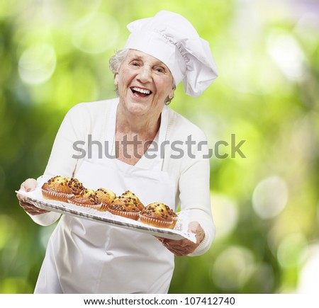 senior woman cook holding a tray with muffins against a nature background