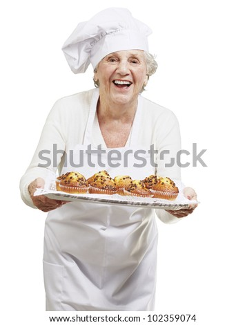 senior woman cook holding a tray with muffins against a white background - stock photo