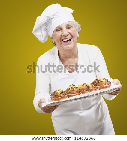 senior woman cook holding a tray with muffins against a yellow background