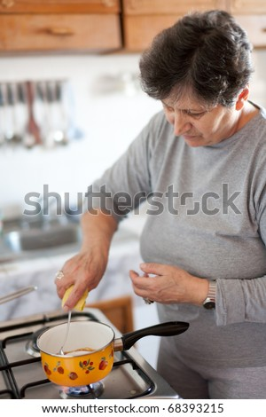Senior woman cooking on a stove in bright daylight