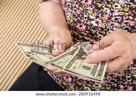 senior woman counting money (american dollars) - stock photo