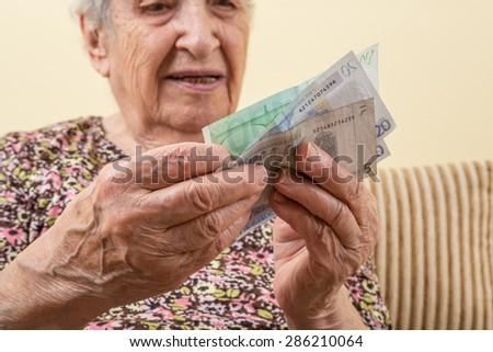 senior woman counting money (euros) - stock photo