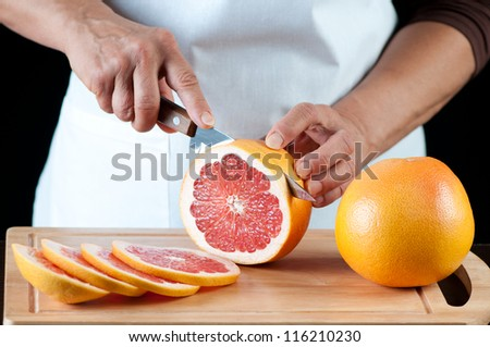 Senior woman cutting grapefruits on a wooden board, studio shot - stock photo