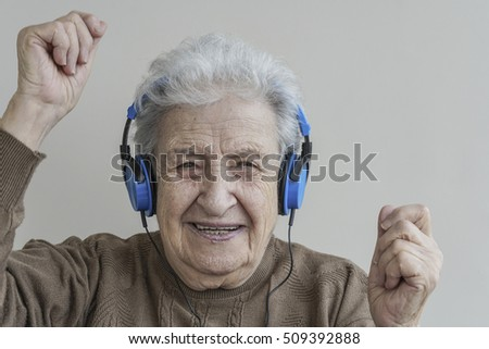 senior woman dancing while listening music with headphones