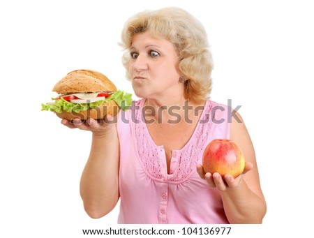 senior woman deciding what to eat a hamburger or an apple isolated on white