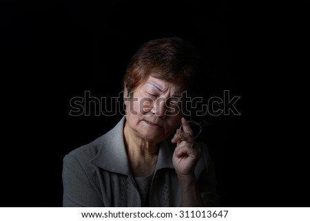 Senior woman displaying pain while holding reading glass on black background.
