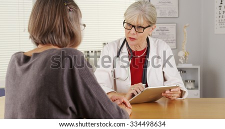 Senior woman doctor talking patient at desk - stock photo