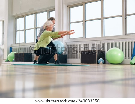 Senior woman doing exercise with her personal trainer at gym. Gym instructor assisting elder woman in her workout. - stock photo