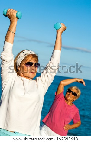 Senior woman doing exercise with weights on beach.