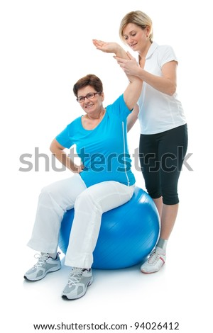 Senior woman doing fitness exercise with help of trainer at sport gym - stock photo