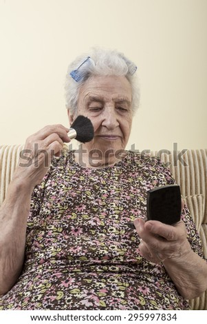 senior woman doing make up - stock photo