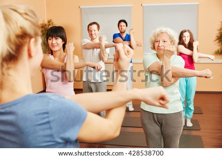 Senior woman doing pilates with a group of people at a fitness center - stock photo