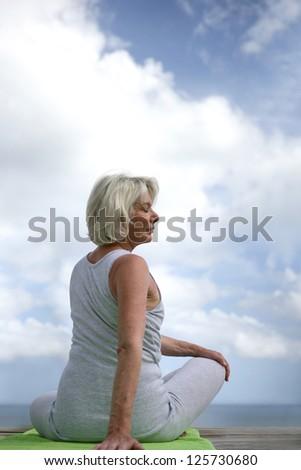 Senior woman doing yoga outdoors - stock photo
