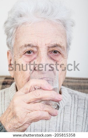 senior woman drinking - stock photo