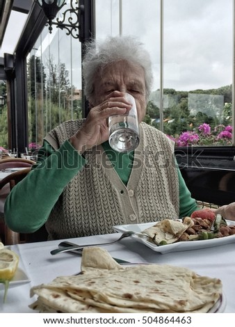senior woman drinking a glass of water while having lunch