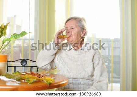 Senior woman drinking juice in her room. MANY OTHER PHOTOS FROM THIS SERIES IN MY PORTFOLIO. - stock photo