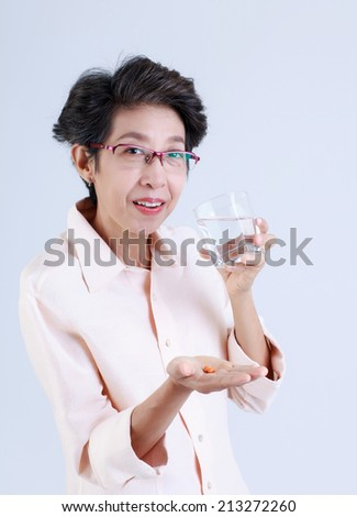 Senior woman drinking water with pills in her hand isolated