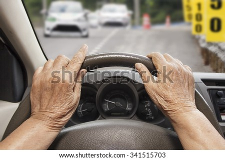 Senior woman driving a car on construction road.