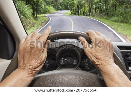 Senior woman driving a car on highway in forest. - stock photo