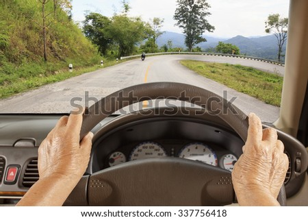Senior woman driving a car slowly on mountain road. - stock photo