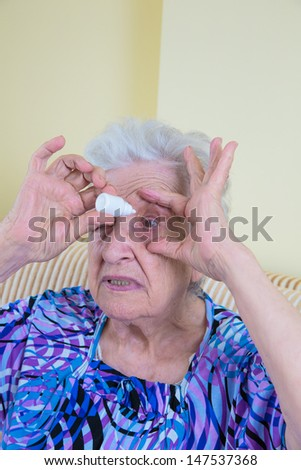 senior woman dropping eye drop by herself - stock photo