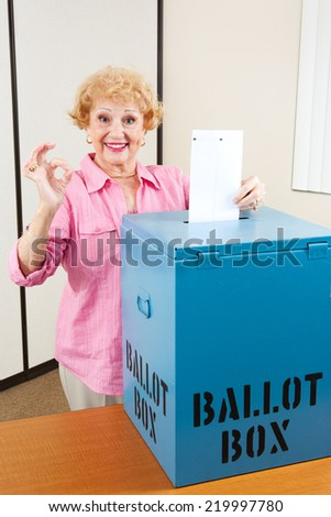 Senior woman drops her ballot in the box and gives A Okay sign.   - stock photo