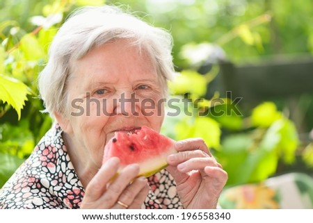 Senior woman eating watermelon in garden. MANY OTHER PHOTOS FROM THIS SERIES IN MY PORTFOLIO. - stock photo
