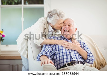 Senior woman embracing man in living room - stock photo