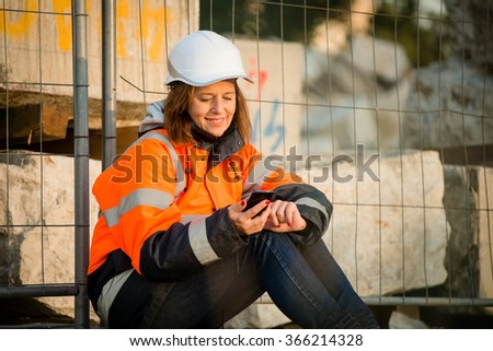 Senior woman engineer in protective workwear relaxing during coffeebreak and looking to phone - stock photo
