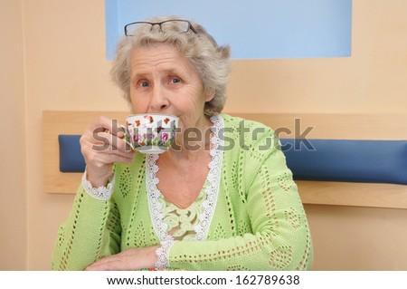 senior woman enjoying coffee or tea cup - stock photo