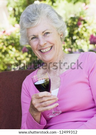 Senior woman enjoying glass of red wine - stock photo