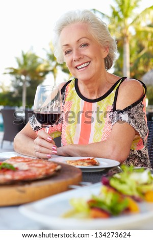 Senior Woman Enjoying Meal In Outdoor Restaurant