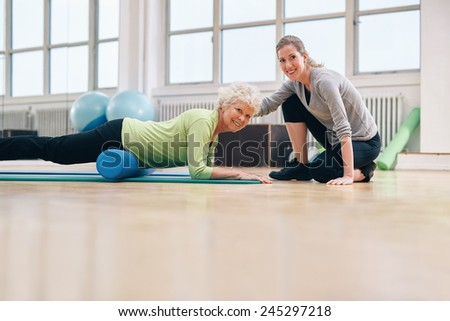Senior woman exercising on a foam roller with a personal trainer at gym.  Gym coach helping elderly woman in her workout at health club. - stock photo