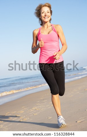 Senior Woman Exercising On Beach - stock photo