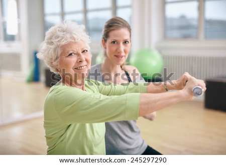 Senior woman exercising with fitness trainer at gym. Active senior woman lifting dumbbells with help from personal trainer. - stock photo