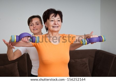 Senior woman exercising with trainer - stock photo