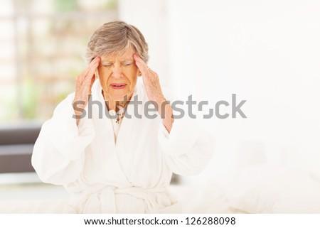 senior woman feeling headache at home - stock photo