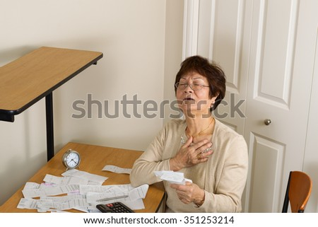 Senior woman feeling ill with her financial bills. In debt concept.  - stock photo