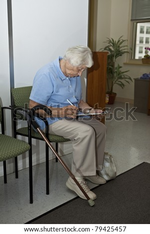 Senior woman filling out forms at the doctor`s office - stock photo