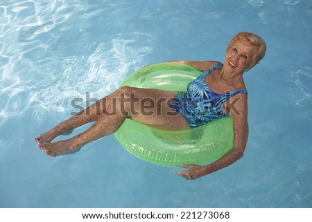 Senior woman floating in swimming pool - stock photo