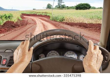Senior woman get lost way  , driving a car slowly on rural road - stock photo