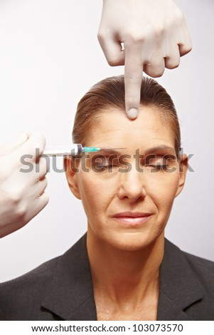 Senior woman getting a syringe injected at plastic surgery - stock photo