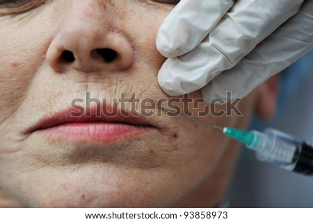 Senior woman getting skin care injection - stock photo