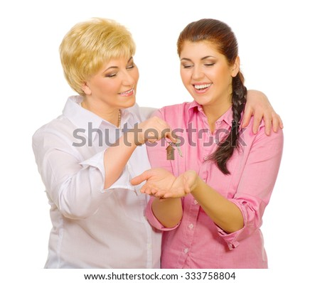Senior woman give keys to her daughter isolated - stock photo
