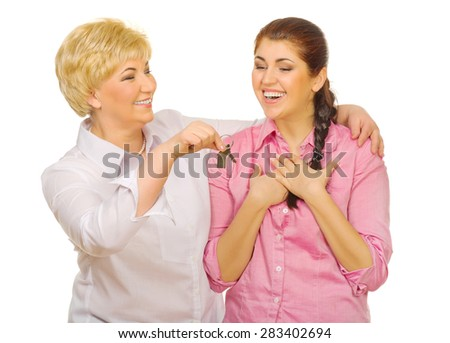 Senior woman giving keys to her daughter isolated - stock photo
