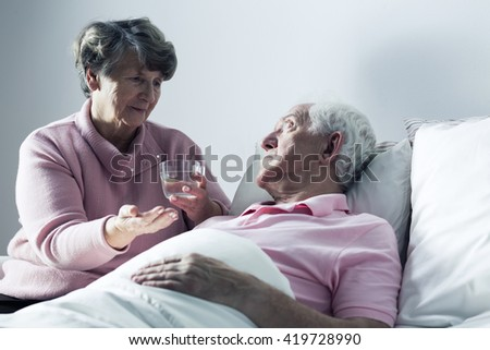 Senior woman giving medicines to her sick husband lying in a hospital bed - stock photo